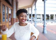 Mulher afro-americano de sorriso que senta-se no restaurante exterior Foto de Stock