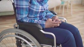 A mulher afro-americano deficiente em uma cadeira de rodas usa um smartphone filme