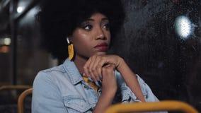 Mulher afro-americano deprimida que monta um transporte público na noite Menina triste que olha para fora a janela Luzes da cidad filme
