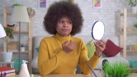 A mulher afro-americano do retrato com um penteado afro dessa vista infeliz no espelho encontra um defeito na pele vídeos de arquivo