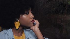 Mulher afro-americano do younf comprimido, triste que monta um transporte público na noite Ela que olha para fora a janela filme