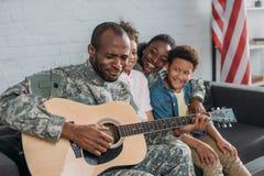 Mulher afro-americano e crianças que escutam para genar na roupa da camuflagem fotografia de stock royalty free