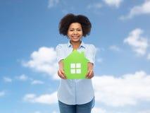 Mulher afro-americano feliz com ícone da casa verde Fotos de Stock Royalty Free