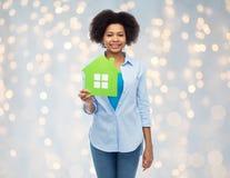 Mulher afro-americano feliz com ícone da casa verde Fotografia de Stock Royalty Free