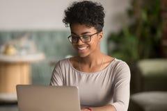 Mulher afro-americano feliz que usa o estudo de trabalho do portátil no escritório imagem de stock