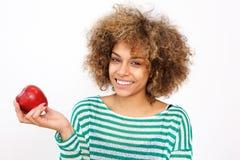Mulher afro-americano nova atrativa que guarda uma maçã foto de stock