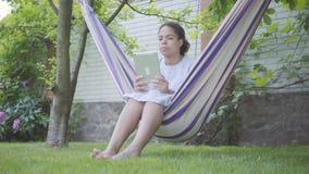 Mulher afro-americano nova bonito do retrato que senta-se na rede, relaxando no jardim, texting em sua tabuleta vídeos de arquivo