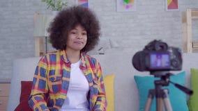 A mulher afro-americano nova com o blogger do penteado do Afro escreve o v?deo na sala de visitas mo lento filme