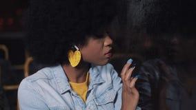 Mulher afro-americano nova comprimida, triste que monta um transporte público na noite Ela que olha para fora a janela filme