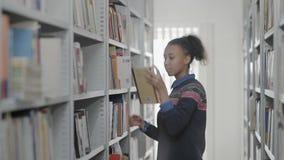 A mulher afro-americano nova está tomando o livro da prateleira da biblioteca escolar filme