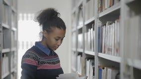 A mulher afro-americano nova está tomando o livro da prateleira na biblioteca video estoque