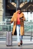 Mulher afro-americano nova feliz do corpo completo que anda na estação com mala de viagem e telefone celular fotos de stock