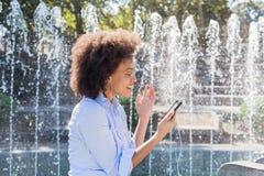 Mulher afro-americano nova feliz no vestuário desportivo, usando Smartphones para a rede social fotografia de stock