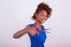 Mulher afro-americano nova que corta seu cabelo afro crespo com s imagem de stock