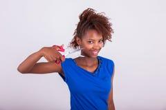 Mulher afro-americano nova que corta seu cabelo afro crespo com s foto de stock