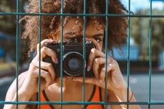 mulher afro-americano nova que está atrás de cercar prendido e de tomar uma imagem imagens de stock