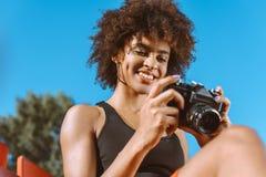 Mulher afro-americano nova que olha a tela de digital imagens de stock