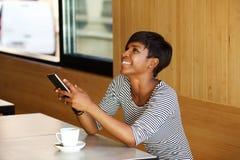 Mulher afro-americano nova que ri com telefone celular Fotografia de Stock Royalty Free