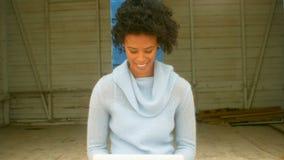 Mulher afro-americano nova que senta e que usa o portátil na cabana da praia video estoque