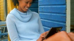 Mulher afro-americano nova que senta e que usa a tabuleta digital na cabana da praia vídeos de arquivo