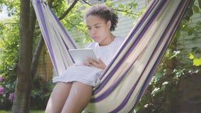 Mulher afro-americano nova que senta-se na rede, relaxando no jardim, texting em sua tabuleta Lazer fora video estoque