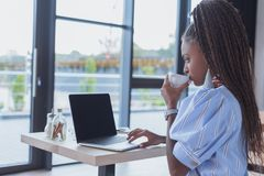 Mulher afro-americano nova que trabalha com portátil e café bebendo foto de stock royalty free