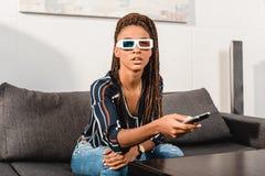 mulher afro-americano pensativa que olha a tevê Imagens de Stock Royalty Free