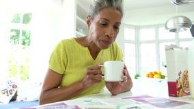 Mulher afro-americano que come o café da manhã e que lê o jornal video estoque