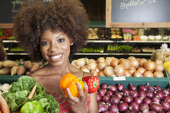 Mulher afro-americano que guarda pimentas e vegetais de sino no supermercado foto de stock