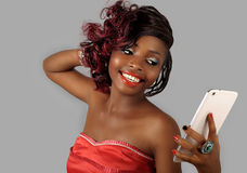 Mulher afro-americano que guarda a tabuleta digital imagem de stock
