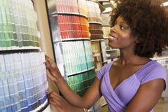 Mulher afro-americano que olha amostras de folha da pintura na loja de ferragens imagem de stock