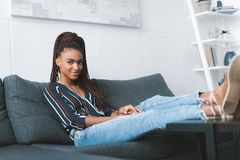 Mulher afro-americano que relaxa no sofá imagens de stock royalty free