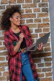 Mulher afro-americano que sorri ao usar o portátil e ao guardar cadernos Imagens de Stock Royalty Free