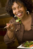 Mulher afro-americano que sorri comendo uma salada Fotos de Stock Royalty Free