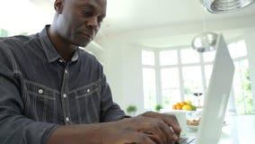 Mulher afro-americano que usa o portátil na cozinha em casa filme