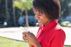 Mulher afro-americano que usa o telefone celular com 4g Fotos de Stock