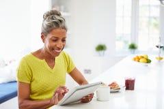 Mulher afro-americano que usa a tabuleta de Digitas em casa Imagem de Stock
