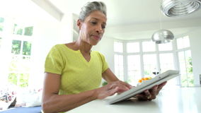 Mulher afro-americano que usa a tabuleta de Digitas em casa video estoque