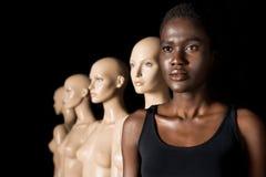 mulher afro-americano séria na posição do roupa de banho na fileira com manequins imagem de stock royalty free