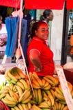 A mulher afro-americano vende a banana imagem de stock