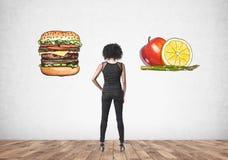 Mulher afro-americano, vista traseira, escolha do alimento imagem de stock royalty free