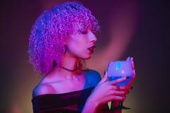 Mulher afro misteriosa que guarda uma bebida da noite no Dia das Bruxas Foto de Stock
