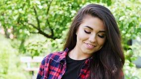 Mulher agrária nova bonita que aprecia a natureza no jardim do verão, menina feliz que sorri e que olha a câmera vídeos de arquivo