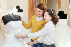 A mulher ajuda o gitl em escolher o vestido nupcial fotografia de stock royalty free