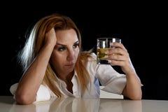 Mulher alcoólica bêbada desperdiçada e terra arrendada comprimida que olha pensativa ao vidro do uísque escocês foto de stock
