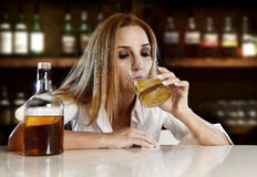 A mulher alcoólica bêbada desperdiçou beber no uísque escocês na barra imagens de stock