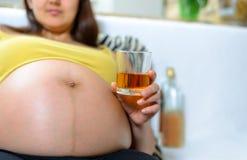 Mulher alcoólica grávida com vidro do licor imagem de stock royalty free