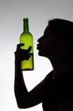 Mulher alcoólica que beija uma garrafa de vinho Fotografia de Stock Royalty Free