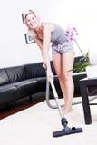 A mulher alegre atrativa está na sala com aspirador de p30. imagem de stock