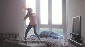 A mulher alegre bonita nova salta e dança na cama no apartamento luxuoso durante o nascer do sol bonito com efeito do alargamento video estoque